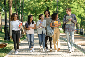 multiethnic group of happy young students walking outdoors